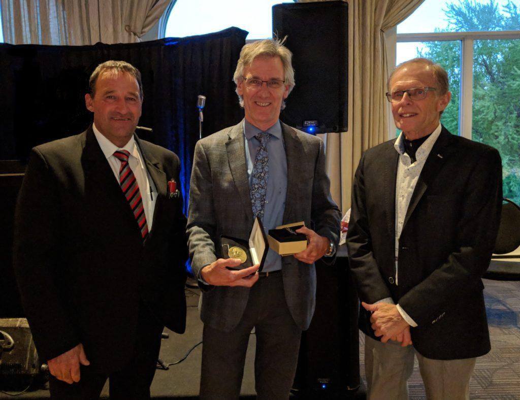 Jean-Pierre Dansereau reçoit le prix Henri-Paul-Gagnon 2019 des mains du premier vice-président et du président de la FPFQ, de MM. Gaétan Boudreault et Pierre-Maurice Gagnon.